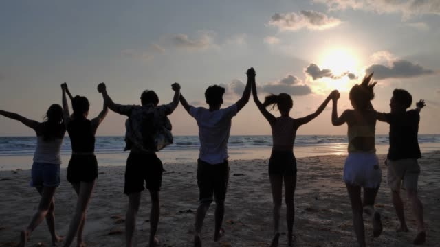 Silhouette group of friends having fun on the beach.Happy smiling friends running seaside sea ocean holiday travel.Vacations - iStock