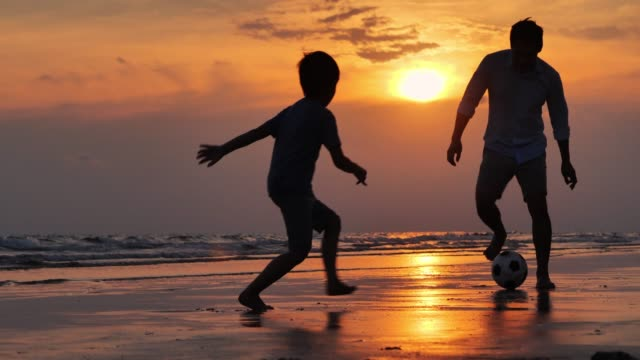 vídeos de stock e filmes b-roll de silhouette happy father and son having fun playing football on the beach at sunset.happy family enjoy summer vacation on the beach.holiday travel concept.vacations - istock - por do sol