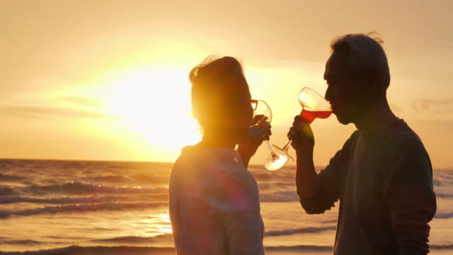 Silhouette happy senior couple having picnic and clinking wine glasses on sunset.Romantic senior couple on summer vacation.Senior couple relaxing by the sea.Senior Holidays,Vacations