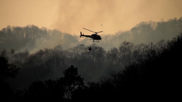Silhouette Helicopter with firefighters throwing water to fire in the wildfire forest