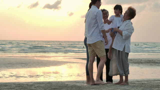 Silhouette joyful asian large family hugging to sunset sea surf on sand beach.Family,Lifestyle,People,Life insurance,Multi-generation, Elderly,Vacations,Relationship,Children,Holiday,Retirement,Healthy care concept. video