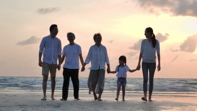 Silhouette joyful asian large family walking to sunset sea surf on sand beach during covid-19 lockdown.Social distancing,Family,Lifestyle,Social distancing. - vídeo