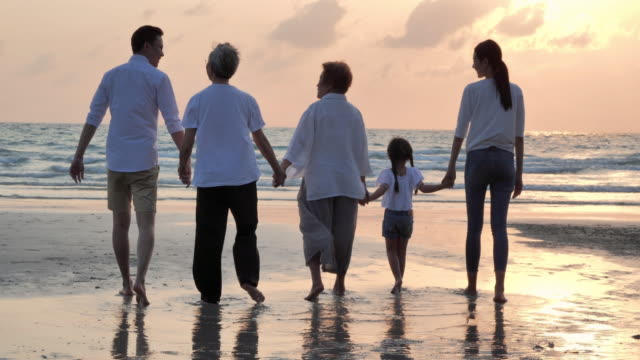 Silhouette joyful asian large family walking to sunset sea surf on sand beach.Family,Lifestyle,People,Life insurance,Multi-generation, Elderly,Vacations,Relationship,Children,Holiday,Retirement,Healthy care concept. video