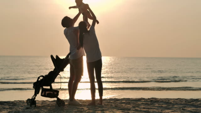 Silhouette joyful father,mother,baby son having fun along edge of sunset sea surf on sand beach.Active parents and people outdoor activity on summer vacations with baby.Happy family holidays.Family,Lifestyle,People,Life insurance,Vacations - iStock - vídeo