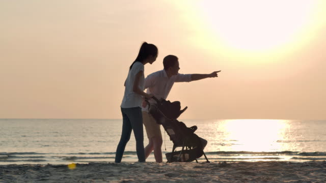vídeos de stock e filmes b-roll de silhouette joyful father,mother,baby son walk with fun along edge of sunset sea surf on sand beach.active parents and people outdoor activity on summer vacations with baby.happy family holidays.family,lifestyle,people,life insurance,vacations - bebé praia