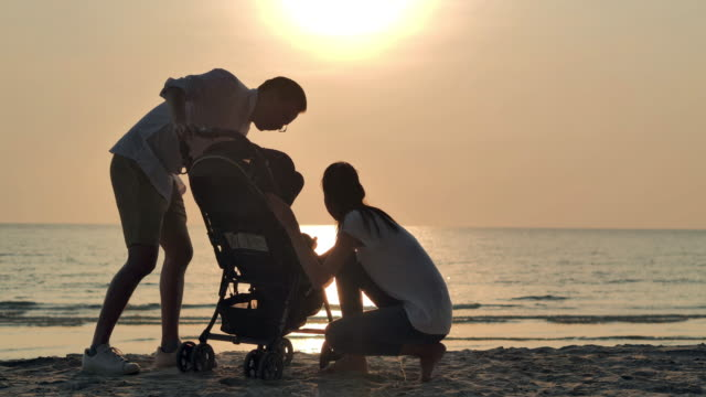 Silhouette joyful father,mother,baby son walk with fun along edge of sunset sea surf on sand beach.Active parents and people outdoor activity on summer vacations with baby.Happy family holidays.Family,Lifestyle,People,Life insurance,Vacations