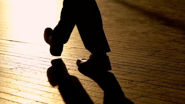 silhouette legs of businessman walking in slow motion - fare un passo video stock e b–roll