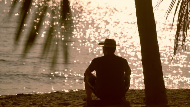 vídeos de stock e filmes b-roll de silhouette - lonely man using under the heat of the sun on a beach - homem chapéu