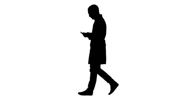 Silhouette Male doctor walking and using mobile phone Full length portrait side view. Silhouette Male doctor walking and using mobile phone. Professional shot in 4K resolution. 004. You can use it e.g. in your commercial video, business, presentation, broadcast silhouette people stock videos & royalty-free footage