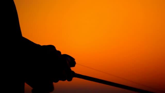 silhouette man fishing - bir orta yetişkin erkek sadece stok videoları ve detay görüntü çekimi