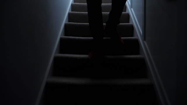 Silhouette man walking downstairs at night. 2. Dark silhouette of a man, lower body walking upstairs in a domestic house. Shot at 60 fps. SM DS. See alternative camera angle as part of a series. low lighting stock videos & royalty-free footage