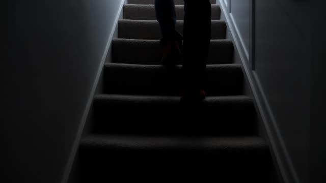 Silhouette man walking upstairs at night. 1.