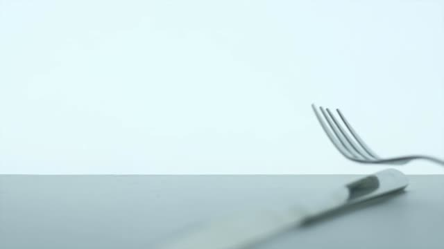 silhouette metallic fork and spoon falling on table on white background silhouette metallic fork and spoon falling on table on white background. slowmotion. fork stock videos & royalty-free footage