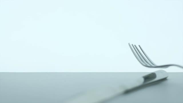 vidéos et rushes de fourchette métallique de silhouette et cuillère tombant sur la table sur le fond blanc - fourchette