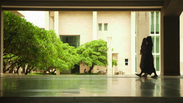 silhouette of 2 muslim girl walk by with reflection - two students together asian video stock e b–roll