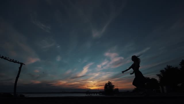 silhouette of a ballerina against the sunset sky. ballerina makes high beautiful jumps. girl in a flowing dress dancing on the street ballet dancer stock videos & royalty-free footage