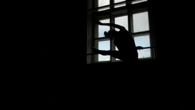 silhuetten av en balettdansös som tränar på barre genom fönstret - balettstång bildbanksvideor och videomaterial från bakom kulisserna