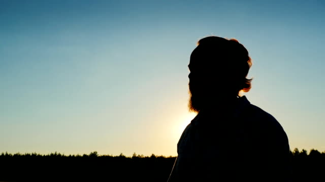 Silhouette of a bearded man who smokes at sunset video