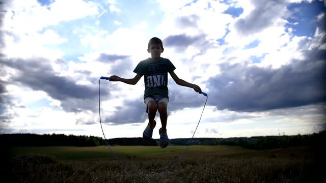 silhouette of a boy jumping rope on the sky background video