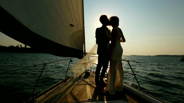 silhouette of a bride and groom kissing on a yacht video