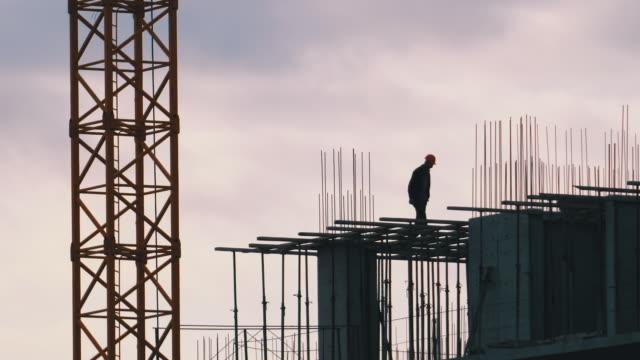 vídeos y material grabado en eventos de stock de silueta de un constructor en el borde de un rascacielos en construcción. trabajadores en una obra de construcción - material de construcción