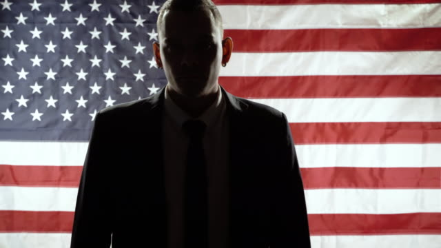Silhouette of a business man walking towards the camera against the background of the American flag. Silhouette of a business man walking towards the camera against the background of the American flag president stock videos & royalty-free footage