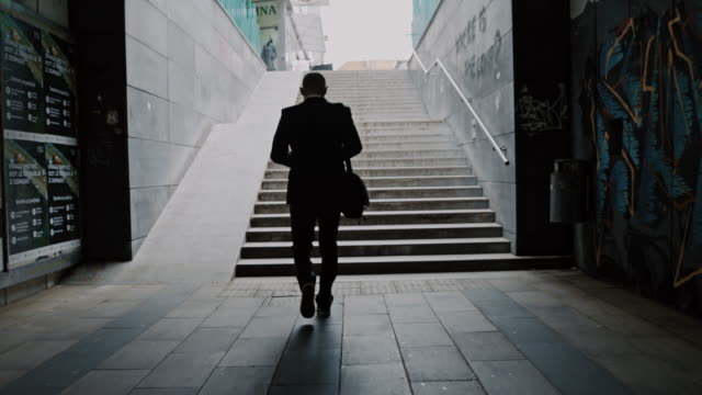 SLO MO Silhouette of a businessman walking out of underpass Slow motion shot of a silhouette of an unrecognizable businessman walking out of underpass. Shoot in 8K resolution. business suit stock videos & royalty-free footage