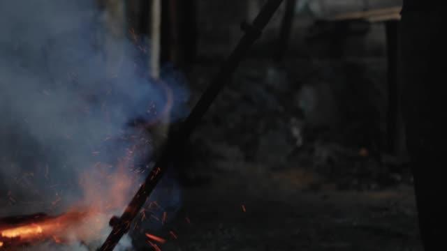 sagoma di un operaio all'interno che lavora con il rame su un fuoco aperto - attrezzatura energetica video stock e b–roll