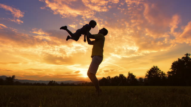 SLO MO DS Silhouette of a father tossing his son into air outside at sunset Slow motion medium low angle dolly shot of a silhouette of a father tossing his son gently into the air in the meadow at sunset. silhouette people stock videos & royalty-free footage