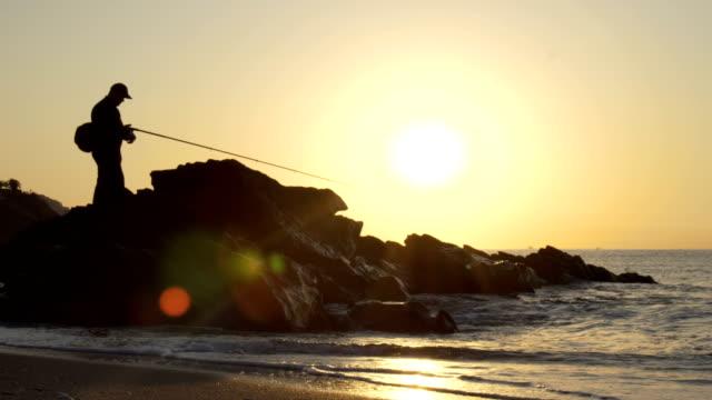 Silhouette eines Fischers, Mann Angeln bei Sonnenuntergang auf einem Meer aus dem Felsen – Video