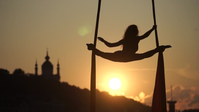 Silhouette of a flexible woman acrobat on aerial silk during a sunset on Kiev city background. concept of freedom and peace