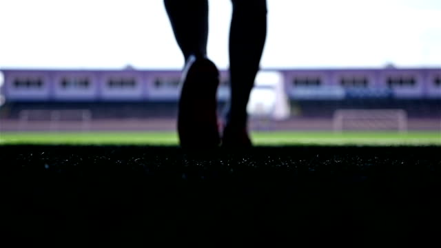 vídeos de stock e filmes b-roll de silhouette of a football player going out to the stadium, slow motion - estádio