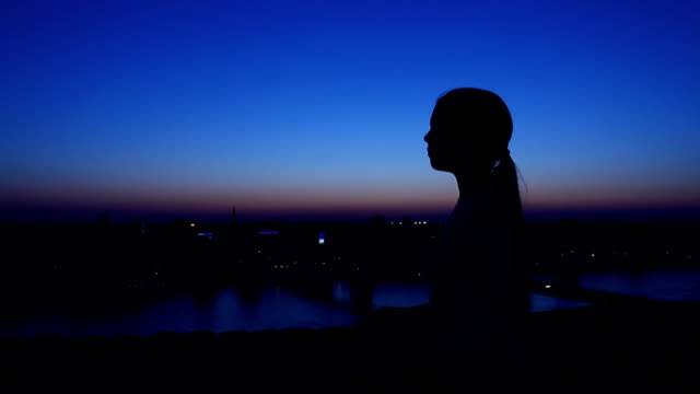 Silhouette of a girl against the evening sky.