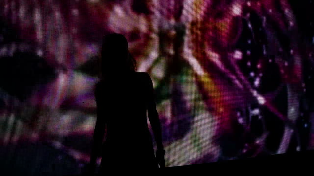 Silhouette of a girl dancing at a party in front of a video wall A girl is dancing at a party in front of a video wall. Only a  silhouette of a dancing girl is visible.  Colorful background is animated on a video wall. She is at a party in a night club. narcotic stock videos & royalty-free footage