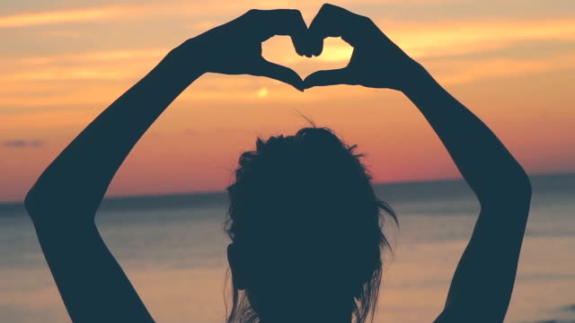 Silhouette of a girl holding a heart-shape. video