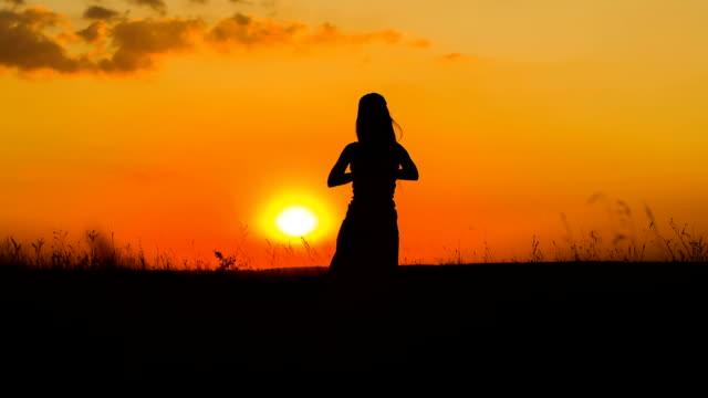 silhouette di una ragazza praticare yoga al tramonto - posizione corretta video stock e b–roll