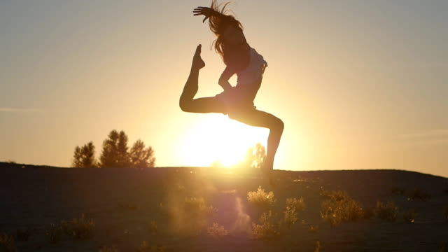 silhouette of a girl professional dancer jumping at sunset in slow motion video