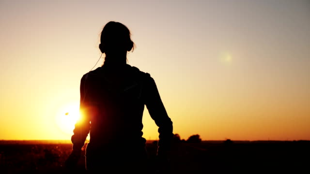 Silhouette of a girl running along the road video