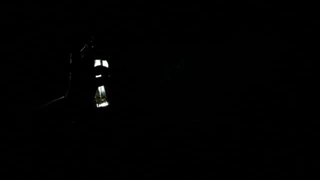 silhouette of a girl spraying perfume in the dark. - profumato video stock e b–roll