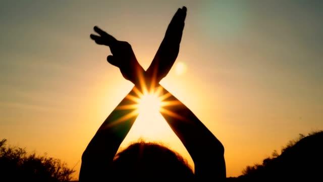 vídeos de stock, filmes e b-roll de silhueta de uma menina com asas ao pôr do sol. a garota dobrado suas mãos sobre a cabeça e acena-lhes como asas contra a luz amarela. - despedida