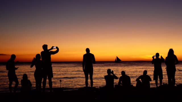 Silhouette of a group of friends having fun on the beach Silhouette of a group of friends having fun on the beach pacific islands stock videos & royalty-free footage