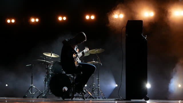A silhouette of a guitarist playing the guitar during a concert on stage.