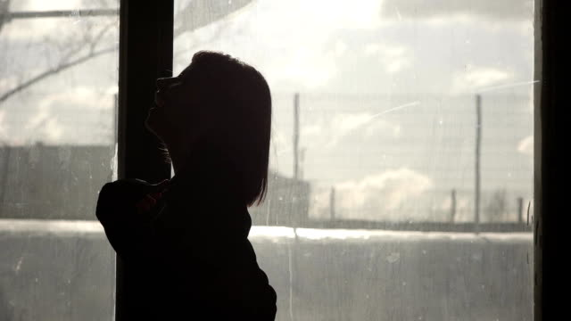 Silhouette of a happy girl dancing in front of a window video