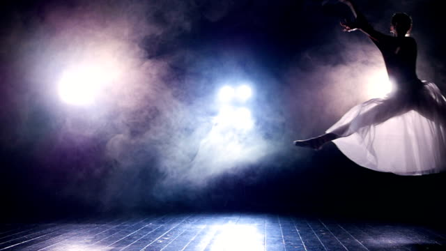 A silhouette of a jumping ballerina on a dark stage. video