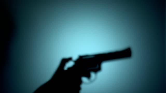 Silhouette of a killer raising revolver, cocking the trigger, shooting a gun