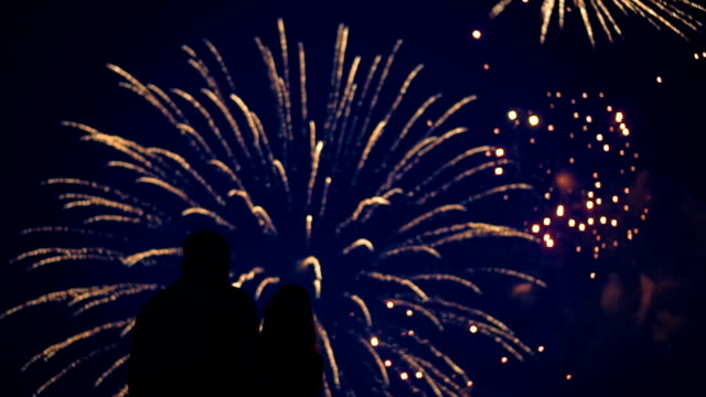 silhouette of a loving couple of people looking at the fireworks. - petardo video stock e b–roll