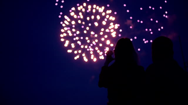 silhouette of a loving couple of people looking at the fireworks. - fireworks stock videos & royalty-free footage