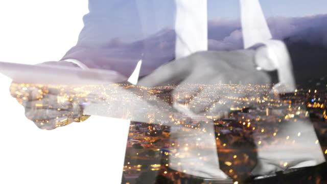 stockvideo's en b-roll-footage met silhouet van een man en digitale tablet met stadslichten overlay - dubbelopname businessman