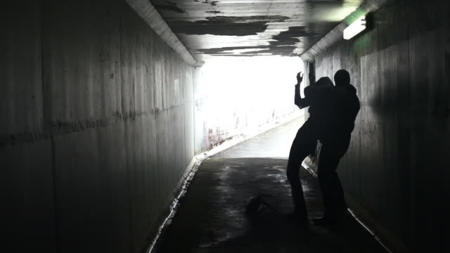 Silhouette of a man attacks a woman from behind in a dark tunnel video