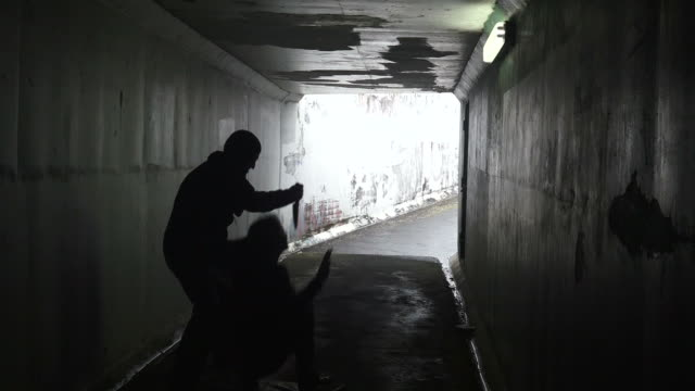 Silhouette of a man attacks  a young woman with a knife in a dark tunnel video